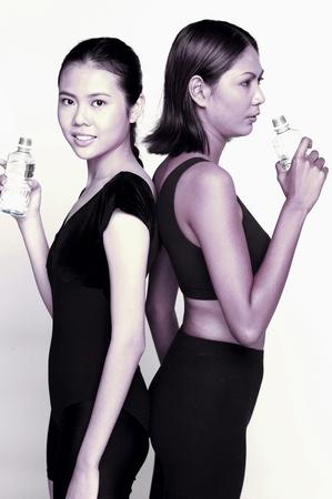 Two women in fitness wear drinking bottled water Stock Photo - 12645809