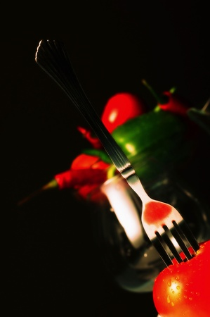 Fork being poked on a tomato with chillies and capsicum on the background Stock Photo - 12645854