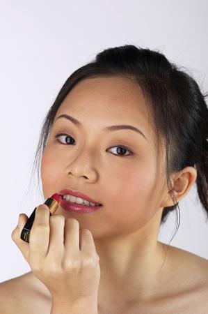 Woman applying lipstick on her lips Stock Photo - 12735745