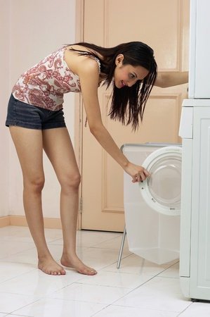 Woman checking the washing machine Stock Photo - 12735804