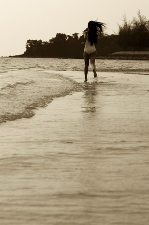 Sepia picture of woman running on the beach Stock Photo - 12735840