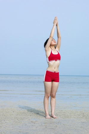 Woman in fitness wear exercising at the beach Stock Photo - 12735861