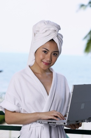 Woman in bathrobe and towel wrapped hair holding a laptop Stock Photo - 12735870