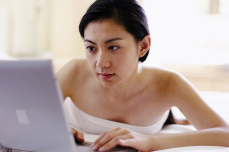 Woman lying on the bed surfing the internet on her laptop Stock Photo - 12735876