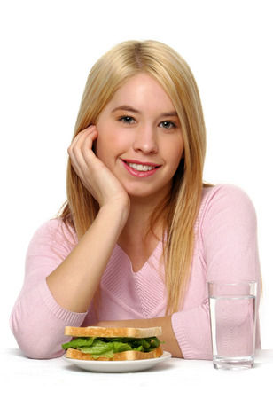 A blonde hair girl sitting at a table posing with a plate of sandwich and a glass of water LANG_EVOIMAGES