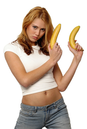 A woman in white shirt and jeans holding up two bananas like holding two guns LANG_EVOIMAGES