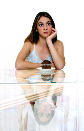 spaghetti strap: A woman posing with a muffin on the table