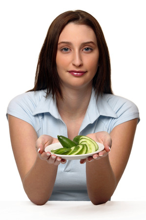 A woman holding up a plate of sliced cucumbers LANG_EVOIMAGES