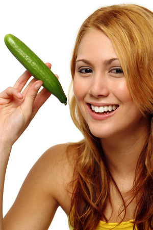 spaghetti strap: A woman in yellow spaghetti top posing with a cucumber while looking at the camera LANG_EVOIMAGES