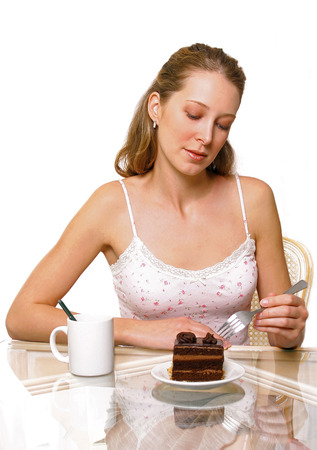 spaghetti strap: A woman looking and holding a fork with a plate of chocolate cake and a cup of water on the table