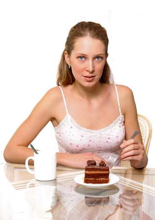 spaghetti strap: A woman holding a fork with a plate of chocolate cake and a cup of water on the table LANG_EVOIMAGES