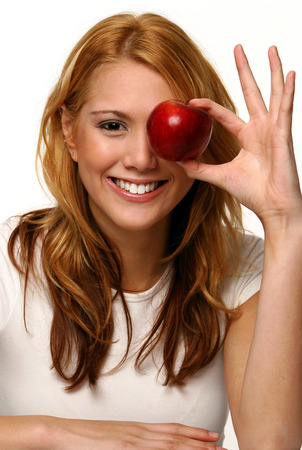 A woman holding up a red apple to cover one of her eyes