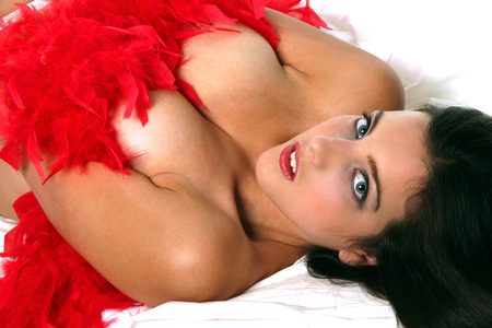 A naked woman lying down with red feathers covering her body