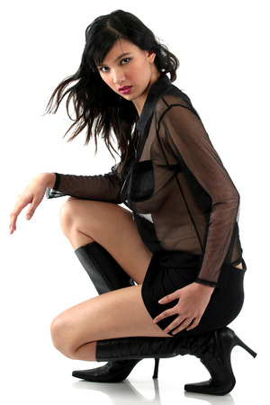 A woman in black squatting down posing for the camera