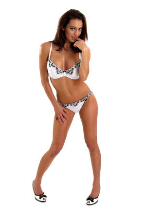 A woman in black and white bikini and matching shoes biting her finger