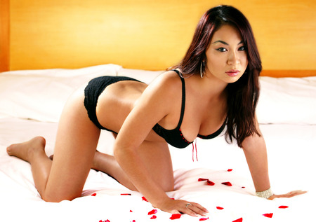A woman in black bikini crouching on the bed with red rose petals