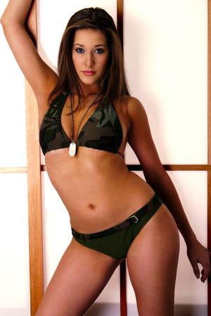 A woman in army bikini leaning against the window with one hand up LANG_EVOIMAGES