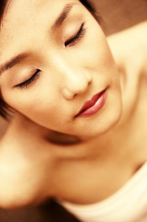 A fair Asian in white tube closing her eyes