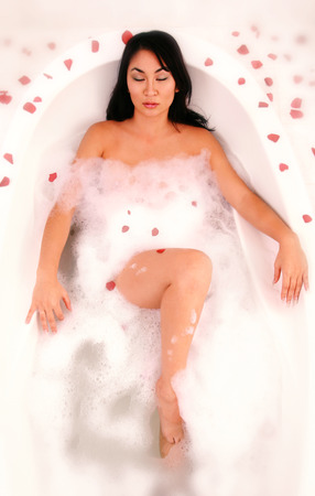 spoiling: An Asian woman relaxing in a bathtub with rose petals everywhere
