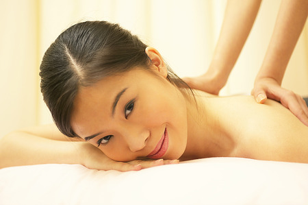 spoiling: A woman lying down as a pair of hands massaging her back