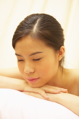 spoiling: An Asian woman closing her eyes while resting her chin on her hands