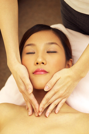 spoiling: An Asian woman lying down with her eyes closed while a pair of hands giving her a facial massage