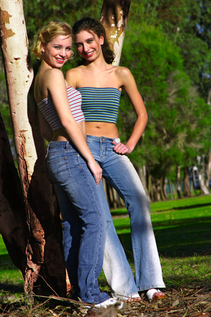 Two woman in tube tops and jeans standing beside a tree Stock Photo
