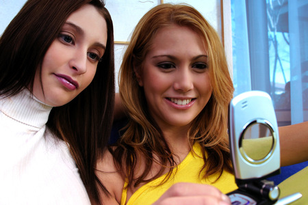 camera phone: Two girlfriends taking picture using a camera phone LANG_EVOIMAGES