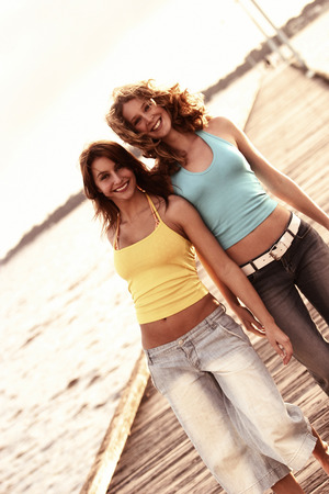 wooden dock: Two friends standing together at a wooden dock LANG_EVOIMAGES