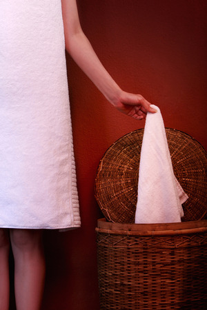 fair complexion: woman holding towel in the laundry LANG_EVOIMAGES