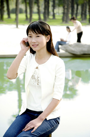 cool gadget: Woman talking on the hand phone LANG_EVOIMAGES