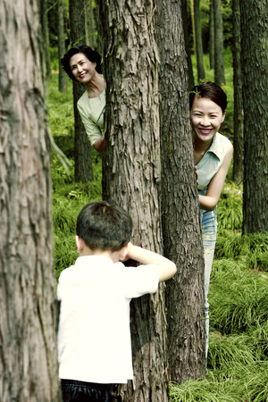 hide and seek: Boy playing hide and seek with his mother and grandmother