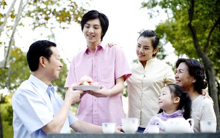 longevity: Man receiving longevity peach from his son LANG_EVOIMAGES