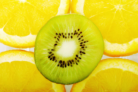 Halved kiwi fruit on four slices of orange