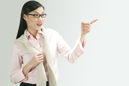 cardigan: Businesswoman with cardigan pointing to the side LANG_EVOIMAGES