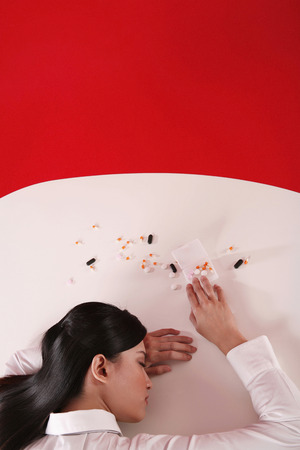 fainted: Businesswoman sitting with her head resting on the table, pills scattered on table