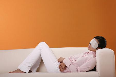 sleep mask: Woman lying on couch, wearing sleep mask