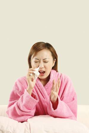 tissue paper: Woman holding tissue paper about to sneeze LANG_EVOIMAGES