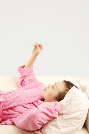 check ups: Woman in bathrobe lying on the couch looking at thermometer