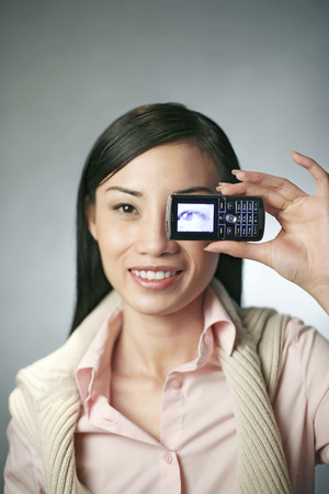 camera phone: Businesswoman taking picture with her camera phone