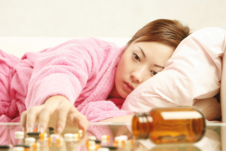 Woman lying on the couch trying to reach scattered pills on the coffee table Stock Photo