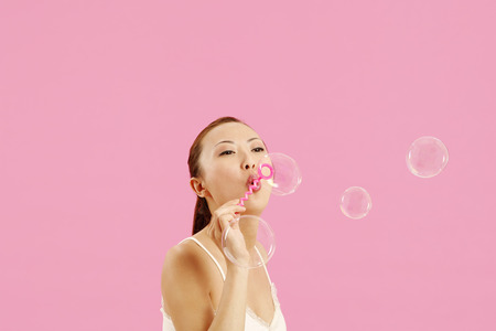 contentment: Woman playing with soap bubbles