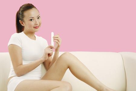 shaping: Woman shaping her fingernail