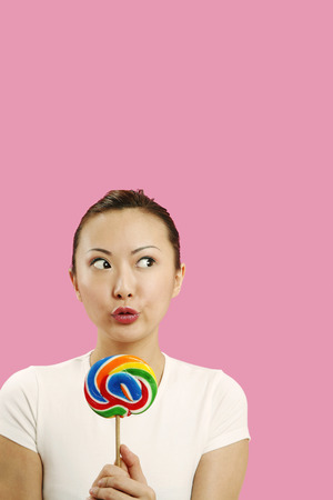 unhealthy thoughts: Woman looking away while holding lollipop