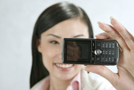 camera phone: Businesswoman taking self picture with her camera phone LANG_EVOIMAGES