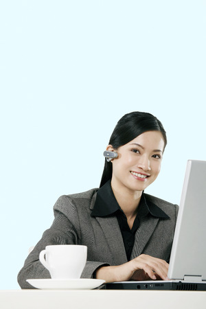 earpiece: Businesswoman with wireless earpiece using laptop