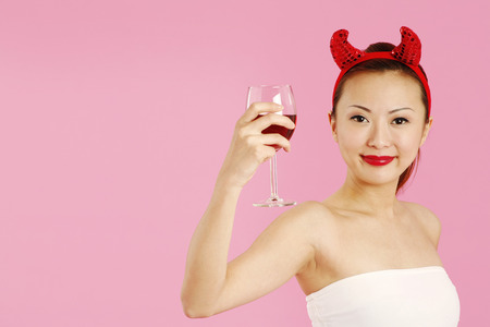 she devil: Woman with devils horns holding a glass of red wine LANG_EVOIMAGES