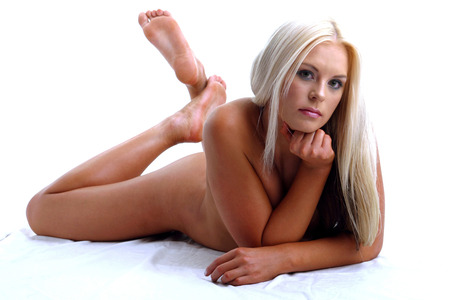 Naked woman lying forward on the bed with her legs up