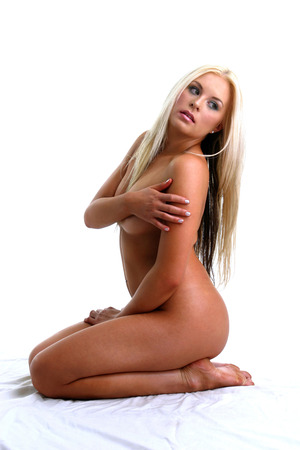 feet naked: Side shot of naked woman kneeling on the bed