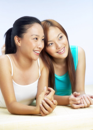 lying forward: Two women with sweet smiles lying forward on the bed